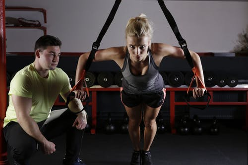 woman and trainer working out to immprove fitness, mental health and nutrition
